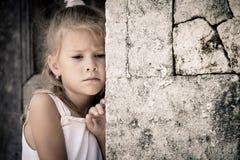 Porträt des traurigen kleinen Mädchens, das nahe Steinwand steht lizenzfreies stockbild