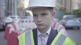 Porträt des traurigen müden kleinen Jungen im Erbauersturzhelm auf seinem Kopf und der Uniform, die weg schaut Gestalt ist Geld stock video