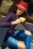 Porträt des trinkenden Kaffees oder des Tees der jungen Schönheit im Freien Stockfoto