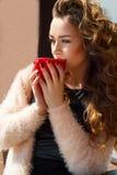 Porträt des trinkenden Kaffees oder des Tees der jungen Schönheit im Freien Stockfotos