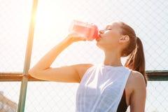 Porträt des trinkenden kalten Wassers der sportlichen jungen sexy Frau von der Flasche auf Sommersportfeld Gesundes Lebensstilkon lizenzfreie stockfotos