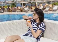 Porträt des trinkenden Safts der jungen Frau auf dem Pool Lizenzfreies Stockfoto