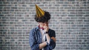 Porträt des unglücklichen Geburtstagsmädchens in der Parteihutstellung kreuzte trauriges Gesicht der Arme stock footage