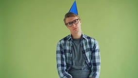 Porträt des unglücklichen jungen Mannes im Parteihut, der Kamera mit traurigem Gesicht betrachtet stock video footage