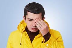 Porträt des unglücklichen müden Mannes des Umkippens versucht, etwas in seinem Verstand zu bedenken, bedeckt Auge mit der Hand, s lizenzfreie stockfotos