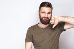 Porträt des unzufriedenen bärtigen Mannes mit den Daumen unten und dunkelgrünem T-Shirt gegen hellgrauen Hintergrund Lizenzfreie Stockfotografie
