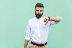 Porträt des unzufriedenen bärtigen Mannes mit den Daumen unten und weißem Hemd gegen hellgrünen Hintergrund Lizenzfreies Stockbild