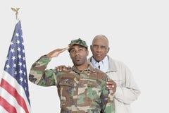 Porträt des Vaters mit Soldat US Marine Corps Begrüßungsamerikanischer flagge über grauem Hintergrund Stockbilder