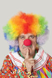 Porträt des verärgerten älteren männlichen Clowns mit dem Finger auf Kinn über hellgrauem Hintergrund Lizenzfreie Stockfotografie