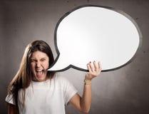 Porträt des verärgerten jungen Mädchens, das eine Spracheblase hält stockfotografie