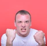 Porträt des verärgerten Mannes schreiend, Faust gegen rotes backgro zeigend Stockfotos