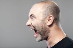 Porträt des verärgerten Mannschreiens lokalisiert auf Grau Lizenzfreies Stockfoto