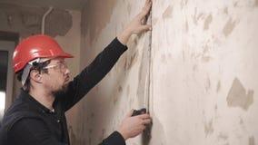 Porträt des Verwalters, Arbeitskraft misst die Zentimeterlänge der Wand stock video