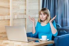 Porträt des verwirrten Freiberuflers des jungen Mädchens mit dem blonden Pendelhaarschnitthaar im blauen T-Shirt sitzen im Café u lizenzfreie stockbilder