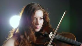Porträt des Violinistmädchens spielt auf hölzerner Geige im Studio auf Hintergrund von Scheinwerfern stock video