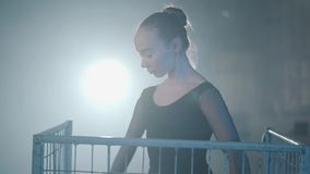 Porträt des würdevollen Berufsballerinatanzens im schwarzen Kleid im Studio innerhalb des blauen Käfigs im Scheinwerfer auf a stock video footage
