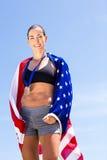 Porträt des weiblichen Athleten eingewickelt in der amerikanischen Flagge Lizenzfreie Stockbilder