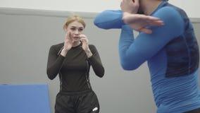 Porträt des weiblichen blonden unerkennbaren athletischen Mannes des Trainers beibringend, wie man Ellbogendurchschlag in muai th stock video footage