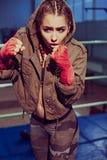 Porträt des weiblichen Boxers in der Sportabnutzung mit kämpfender Position gegen Scheinwerfer Blondes Mädchen der sexy Eignung i Stockfotografie