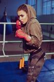 Porträt des weiblichen Boxers in der Sportabnutzung mit kämpfender Position gegen Scheinwerfer Blondes Mädchen der sexy Eignung i Stockbild