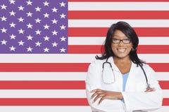 Porträt des weiblichen Chirurgen der überzeugten Mischrasse über amerikanischer Flagge Stockbild