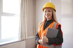 Porträt des weiblichen Feldmessers In Hard Hat und der hohen Sicht-Jacke mit Digital-Tablet-Durchführungshaus-Inspektion lizenzfreie stockfotos