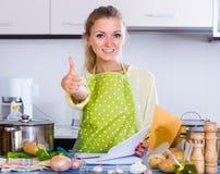 Porträt des weiblichen Freiberuflers mit Dokumenten am Küchentisch Lizenzfreie Stockfotos