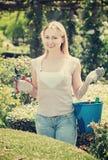 Porträt des weiblichen Gärtners grüne Hecke im Yard trimmend lizenzfreie stockfotografie