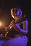 Porträt des weiblichen Gitarristen durchführend im Musikkonzert Lizenzfreies Stockbild