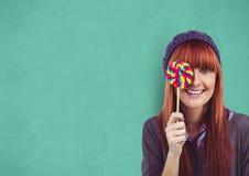 Porträt des weiblichen Hippie-Bedeckungsauges mit Süßigkeit gegen grünen Hintergrund Lizenzfreies Stockfoto