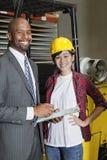 Porträt des weiblichen Industriearbeiters, der mit männlichem Inspektor steht Stockbilder