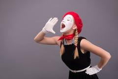 Porträt des weiblichen Pantomimen im roten Kopf und mit Weiß Lizenzfreie Stockbilder