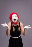 Porträt des weiblichen Pantomimen im roten Kopf und mit Weiß Stockfotos