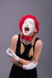 Porträt des weiblichen Pantomimen im roten Kopf und mit Weiß Lizenzfreies Stockfoto