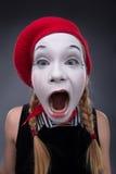 Porträt des weiblichen Pantomimen im roten Kopf und mit Weiß Lizenzfreies Stockbild