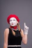 Porträt des weiblichen Pantomimen mit rotem Hut und Weiß Lizenzfreies Stockbild