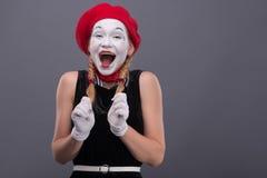 Porträt des weiblichen Pantomimen mit rotem Hut und Weiß Stockfotografie