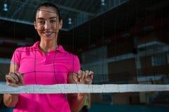 Porträt des weiblichen Volleyballspielers hinter Netz Lizenzfreie Stockfotos