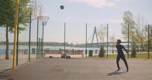 Porträt des werfenden Balls des sportlichen attraktiven Basketball-Spielers des Afroamerikaners männlichen in ein Band und in ein stock video footage