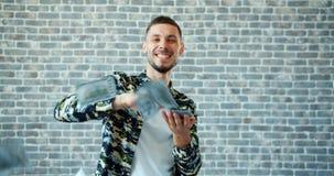 Porträt des werfenden Bargeldes und des Lächelns des jungen Mannes auf Backsteinmauerhintergrund stock video footage