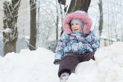 Porträt des Winters im Freien des Lachens des kleinen Mädchens, das auf Schneehügel sitzt Stockfotografie