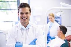 Porträt des Zahnarztes stehend mit den Armen gekreuzt stockfotografie