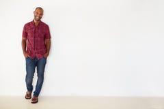 Porträt des zufällig gekleideten Mannes, der an der weißen Wand sich lehnt Lizenzfreie Stockfotografie