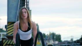 Porträt, die Junge, athletisch, Frau, führt Stärkeübungen mithilfe eines starken, sportlichen Seils durch An der Dämmerung entlan stock video footage