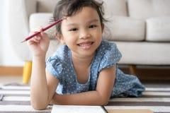 Porträt ein kleines nettes Mädchen studiert die neue Lektion, das Lächeln, nett lizenzfreie stockfotos