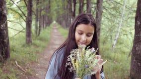 Porträt Ein kleines schönes Mädchen geht auf die Natur, die einen Blumenstrauß von Blumen in ihren Händen hält und ihn betrachtet stock video footage