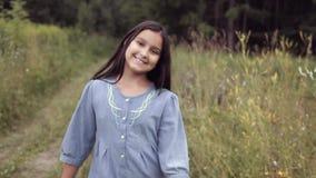 Porträt Ein kleines schönes Mädchen geht entlang den Weg im Wald und lächelt süß stock video