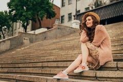 Porträt ein schönes Mädchen in einem Hut, sitzt auf Schrotten hält das Haar vom Wind Weg um die Stadt Porträt eines rothaarigen g lizenzfreies stockbild