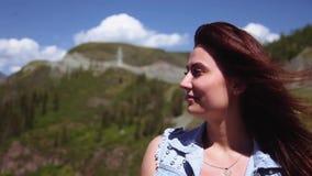 Porträt Ein schönes Mädchen sitzt auf einer Höhe und bewundert die schöne Natur Der Wind brennt ihr Haar durch langsam stock video
