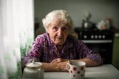 Porträt einer älteren einzigen Frau, die am Tisch sitzt lizenzfreies stockbild